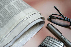 Newspaper & gadgets. Newspaper, spectacles, pen & mobile phone Royalty Free Stock Photography