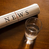 Newspaper and glass of water Royalty Free Stock Image