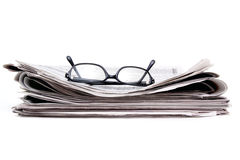 Newspaper and glasses. Reading glasses on stack of newspaper Royalty Free Stock Images