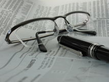 Newspaper with glasses and pen Royalty Free Stock Photography