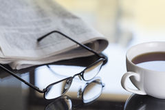 Newspaper and glasses on table Royalty Free Stock Photo