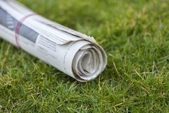 Newspaper on green grass outdoors background royalty free stock photos