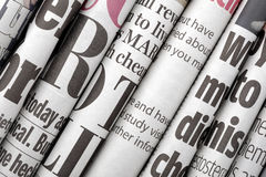 Newspaper headlines. Shown side on in a stack of daily newspapers Stock Photography