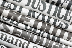 Newspaper headlines. Side on in a stack of daily newspapers Royalty Free Stock Images