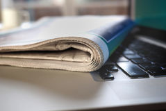 Newspaper on top of a keyboard of laptop Royalty Free Stock Photos