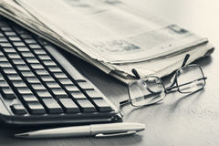 Newspaper with keyboard on table Royalty Free Stock Photo