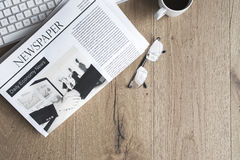 Newspaper with keyboard on table Royalty Free Stock Photography