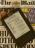 Newspaper on Kindle Electronic E-Reader. An Amazon Kindle ereader which has a newspaper downloaded onto it with a copy of the same physical newspaper edition in Royalty Free Stock Image