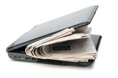 Newspaper and a laptop Stock Image