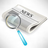 Newspaper with magnifying glass Stock Photo