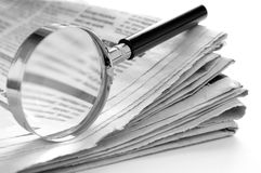 Newspaper and a magnifying glass Royalty Free Stock Images