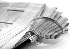 Newspaper and a magnifying glass Stock Photo