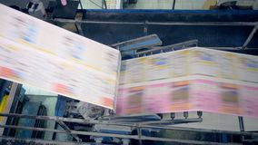 Newspaper moving on a typographical conveyor, top view. A conveyor moves newspaper in printing office
