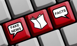 Newspaper News: Fake News or Facts. Red computer keyboard with newspaper icon showing Fake News or Facts royalty free stock photo