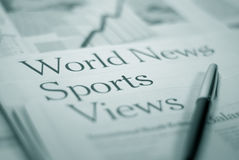 Newspaper pages. `world news` `sports` `views` with a pen Stock Images