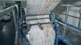 Newspaper pages rolling on mechanical conveyor at a print office. 4K stock footage