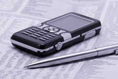Newspaper with pen and mobile phone. Economic newspaper with pen and mobile phone Stock Photo