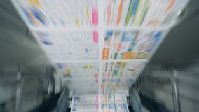 Newspaper sheets moving on a rolling conveyor in typographical facility. 4K stock video
