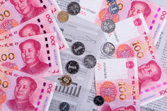 Newspaper showing economic reports covered by Chinese money, sym Royalty Free Stock Image