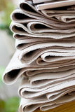 Newspaper stack. A stack of newspapers with focus on front Stock Image