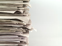 Newspaper Stack. Old newspapers stacked from the top to bottom on the left side of the frame isolated on white Royalty Free Stock Photography