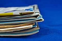 Newspaper stack on blue background Stock Photography