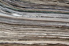 A stack of old newspapers lie on a table royalty free stock images