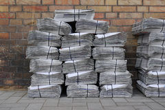Newspaper stack on street. Stacked and bundled tabloid newspapers on sidewalk Royalty Free Stock Image