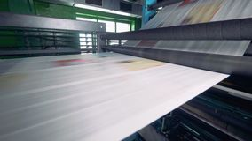 Newspaper strip on a printing machine. Detailed view on a printing machine in action. Newspapers passing near camera. stock video footage