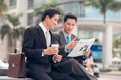 Newspaper. Two Asian businessmen discussing article in the newspaper Royalty Free Stock Photo