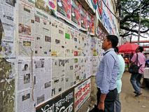 Daily newspaper on the wall in the streets of Dhaka stock photography