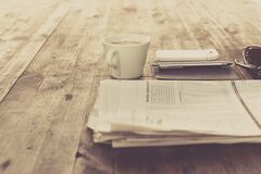 Newspaper and White Ceramic Cup on Brown Wooden Table Stock Image