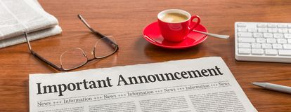 Important announcement. A newspaper on a wooden desk - Important announcement stock photography