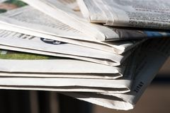 Newspapers. Pile of newspapers in the sunshine Stock Image