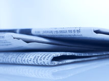 Newspapers. Stack of newspapers isolated on blue Stock Photo