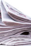 Newspapers Detail. Close up view of stacked newspapers on white background Stock Images