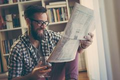 Newspapers and drink. Handsome young man reading newspapers and having a drink in his home library stock photos