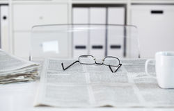 Newspapers with eyeglasses on table Royalty Free Stock Image