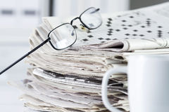 Newspapers with eyeglasses on table Stock Photography