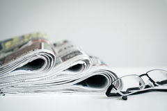Newspapers with eyeglasses on white background royalty free stock photos