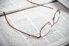 Newspapers and glasses. News newspaper and glasses on the newspaper background Stock Photo
