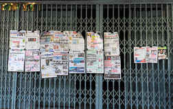 Newspapers hanging on steel door in the morning Royalty Free Stock Photography