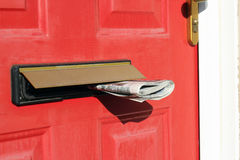 Newspapers delivery in letterbox in a red door. Royalty Free Stock Photography
