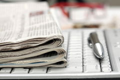 Newspapers on notebook keyboard Royalty Free Stock Photo