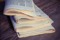 Newspapers on old wood background. Toned image. Royalty Free Stock Photo