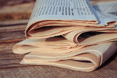 Newspapers on old wood background. Toned image. Royalty Free Stock Images