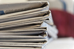 Newspapers pile. Pile of newspapers viewd on their folded ends with a red background with a shallow depth of field. Copyspace Royalty Free Stock Images