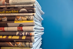 Newspapers piled up. A stack of newspapers with a blue background Royalty Free Stock Images