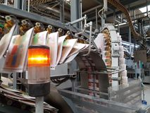 Newspapers printed in industrial printing press. On a chain conveyor printed newspapers are transported for the media Stock Photos