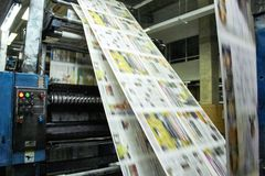 Line of printed newspapers. Newspapers printed in their final process ready to be packed and delivered, in the cities of the world royalty free stock images